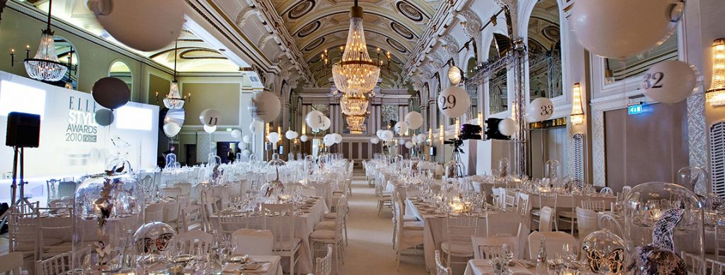 Venue with white chairs and chandelier